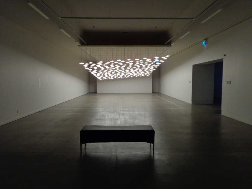 A long gallery corridor with a dark concrete floor, which has a single black bench placed in the centre foreground. At the other end of the corridor hangs masses of identical ceiling lights, which slant upwards at one end giving a tilted effect. They shine downwards and reflect light onto the floor below.