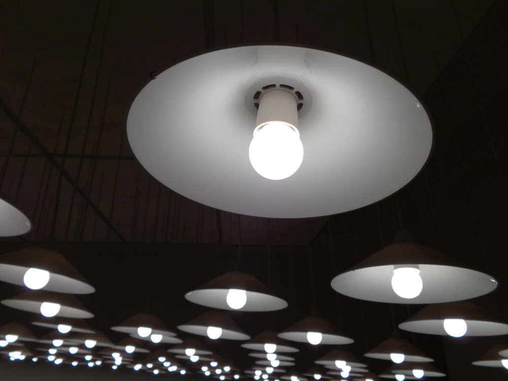 A close up detail of one of the light fixtures as described in the image above. The light is black, circular and has a single glowing white bulb in the middle.