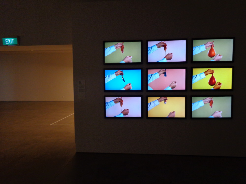 Nine identically sized television screens are mounted in a grid on a darkened wall. Each screen has an almost identical still image of a person's hands popping a balloon. Each screen's video is slightly delayed so that two show the balloon still intact, and the others show it in various stages of popping. The background of each video is a different shade of pastel blue, pink, purple, orange or green.