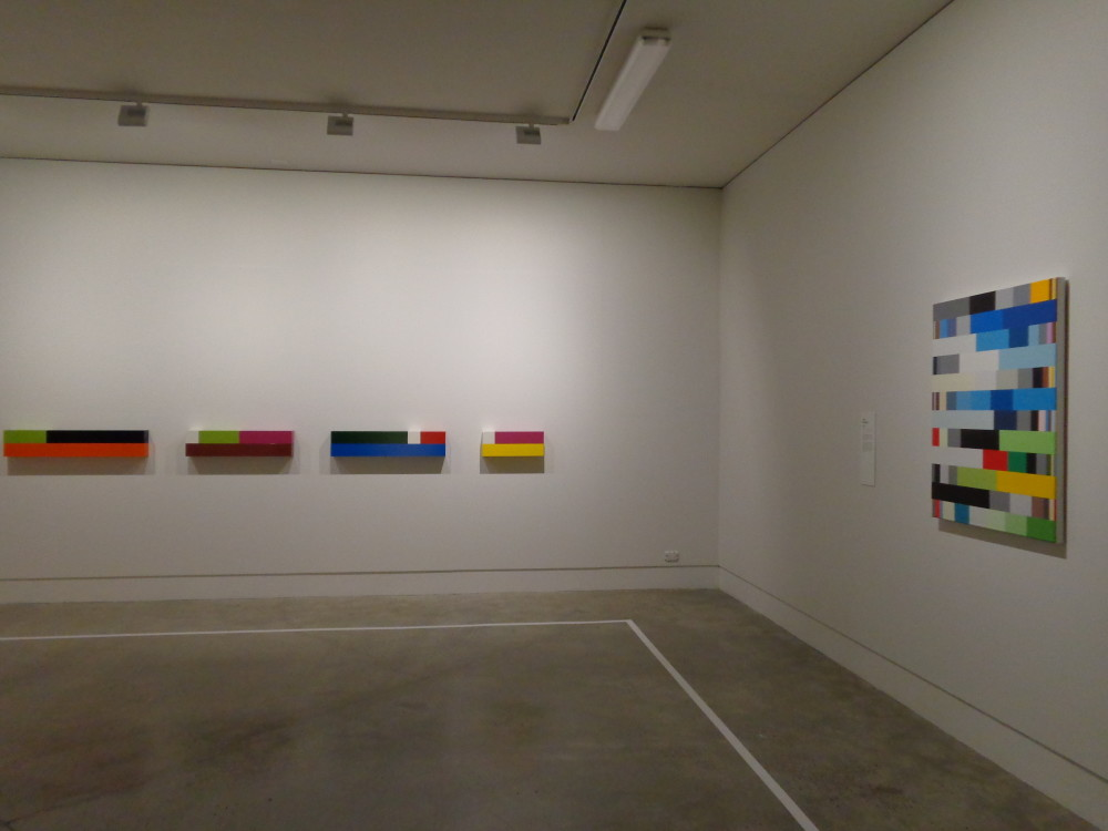 The image shows the corner of a gallery room. On the left is a series of giant cuisenaire rods stacked on top of one another, all in different colours, to form four individual oblong works. On the right is a visually similar artwork, a canvas painted with long colourful horizontal strips with white inbetween.