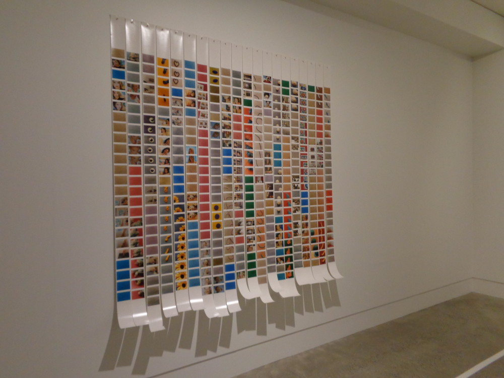 Multiple long strips of photographic glossy paper are pinned to a gallery wall, with their ends hanging loose and curling upwards. The strips have small photographs printed on them, with multiple photos being repeated in a line. Photographs include a close up of a sunflower, blue sky and people, but are too small to see clearly. The overall effect is of a colourful grid.