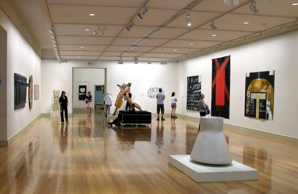 The image shows a white gallery space with a polished wooden floor. In the centre of the room, a sculpture of a grey concrete triangular shape sits on a flat plinth. On the walls around the sculpture hang multiple artworks of various sizes and colours, with people standing around in the space contemplating them.