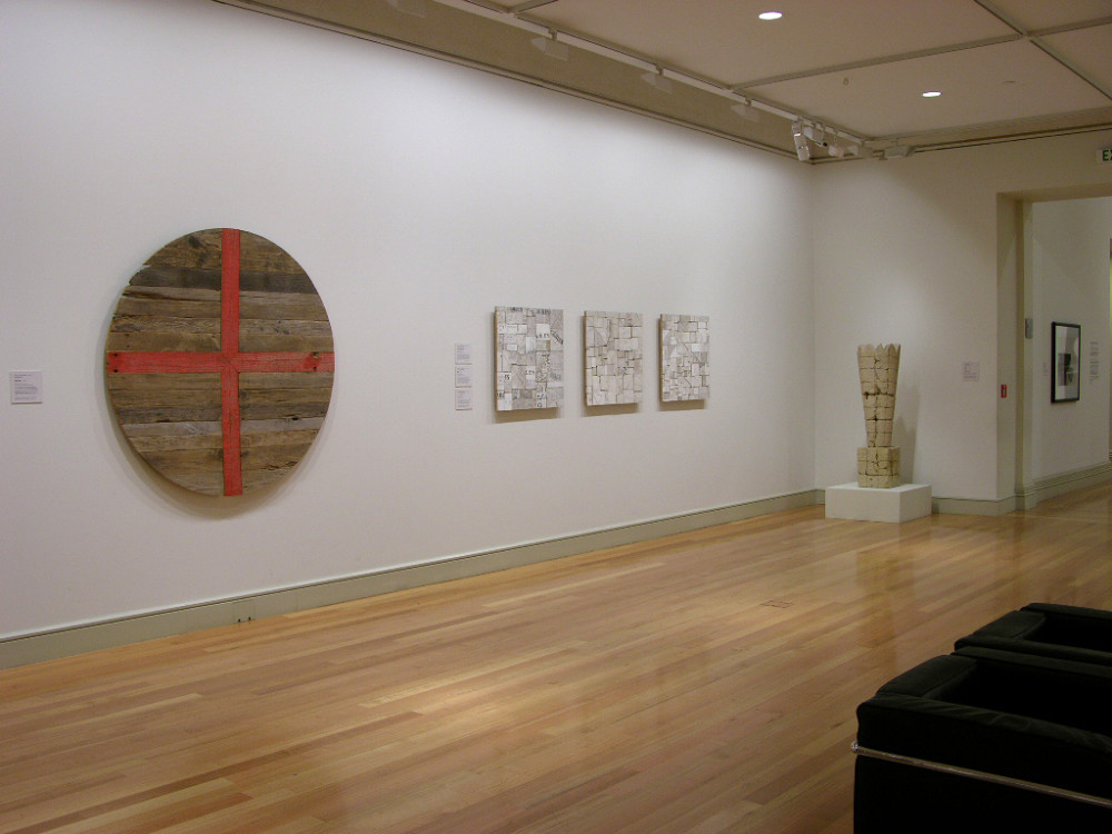 The image shows artworks hanging on a wall. On the left hangs a large circle of wood with a bright orange cross painted through it. Next to this hang three small artworks comprised of lots of small pieces of chopped wood arranged together and whitewashed. On the right stands a large abstract sculpture which tapers outwards.