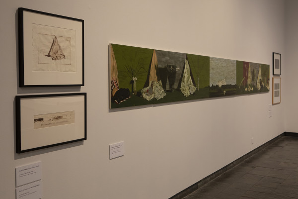 The image shows a gallery wall in Waikato Museum. On the left are two drawings in square frames which appear to be studies for the main, large painting next to them. The large painting is a long horizontal work stretching away from the viewer, showing objects arranged in still life compositions against light green backgrounds with landscapes in between.