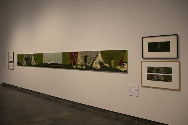 The image shows a gallery wall in Waikato Museum. On the left is a long horizontal painting stretching away from the viewer, showing objects arranged in still life compositions against light green backgrounds with landscapes in between. On the right are two framed studies for the work.