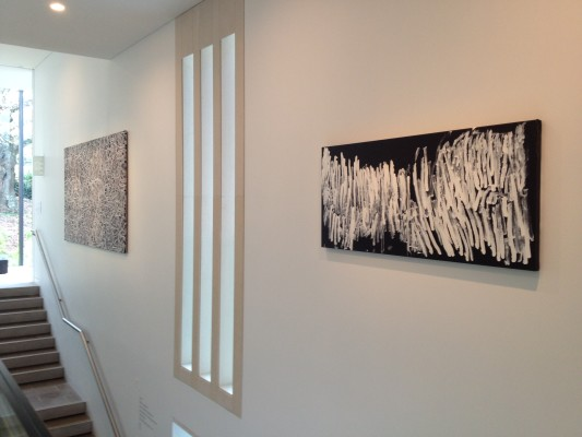 The image shows a gallery wall next to a staircase in Auckland Art Gallery. A vertical slatted window is in between two artworks. On the left is Bush Yam Dreaming, a work of grey circular spiralling shapes over a black background. On the right is a work by Dawn Naranatjil Yakuri, consisting of a black horizontal rectangular canvas with lots of long painted slashes of white paint filling the majority of the canvas.