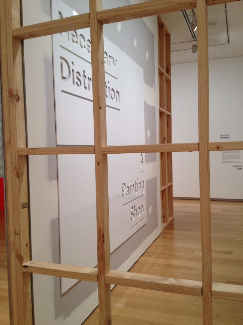 An image of the first wall of the exhibition. A wooden grid is in the foreground, and through it an unpainted gib board wall can be seen with a large white sign mounted on it. The sign reads 'Necessary Distraction, A Painting Show'.