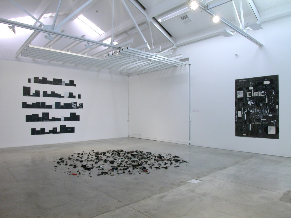 The image shows a white gallery space with a concrete floor. On the left hand wall is an artwork consisting of multiple horizontal rows of small books, which are all varying heights and widths. The shelves are arranged in so that the edges of the entire installation look rounded off in an almost circular shape. The books are a mixture of black, grey and white and have indiscernible words on them. On the floor in the centre of the room is a work which consists of lots of little, miscellaneous mechanical parts in black and silver scattered haphazardly around in a circular arrangement. On the righthand wall is a large black, vertical artwork which has rectangular shapes in dark grey scattered across it, with the words 'clinic of phantasms' written in the centre.