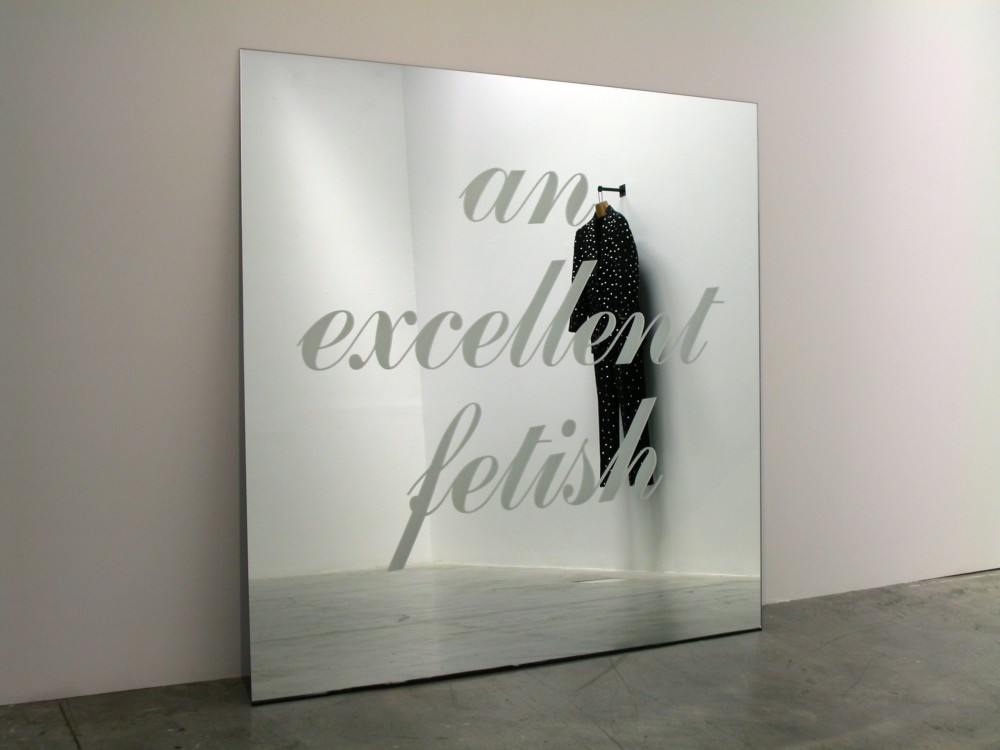The image shows a square mirror leaning against a wall with the words 'an excellent fetish' engraved upon in it cursive writing. A black men's suit covered in little metal studs, hanging from a wall is visible in the reflection of the mirror.