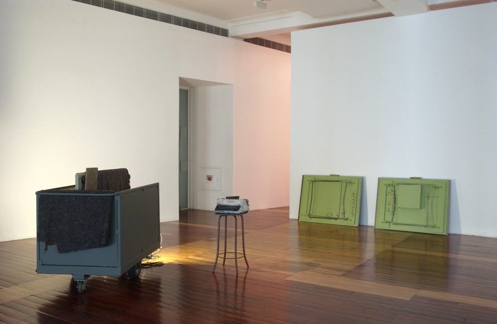 The image shows a white gallery space with a polished wooden floor. On the left hand side of the room sits a large deep trailer on wheels, holding some thin rectangular cargo covered in a grey packing cloth. Light is emitting from a source obscured by the trailer. To the right of the trailer a white and black typewriter perches on top of a tall barstool. Against the right hand wall in the background of the photo two large, rectangular trestle tables are leant against the wall on their fronts, exposing the apple green back of each table to the viewer. Indiscernible writing is messily scrawled upon each table.