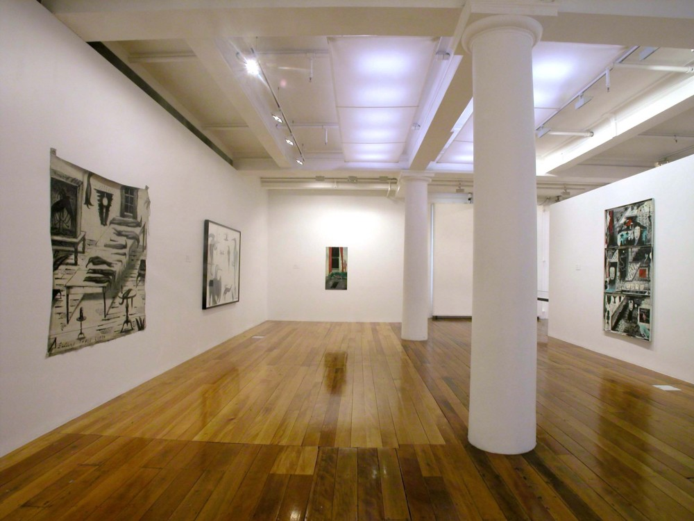 The image shows a white gallery space with a polished wooden floor. Two white columns are in the centre of the room, stretching from floor to ceiling. On the left hand wall hangs a large square artwork which depicts a scene inside a home. An oblong table holds stylised birds of varying sizes and lengths stacked neatly in rows, while three more hang in a clump from the ceiling. Two taxidermied huia birds, with long beaks, are perched stiffly in a large glass vitrine to the left of the table. A glowing lamp and window looking out into a dark night are also present in the work. Across the bottom, the title of the painting, 'Buller's Tablecloth' is written in capital letters. To the right of this painting, another work can just been seen in a large horizontal black frame. This work is also filled with multiple, humanoid birds with long beaks and human arms and hands. Some have wings extending out of their backs, like angels. All are looking in different directions. On the back wall of the gallery hangs a tall vertical painting which depicts a living room space. On a green couch in the living room a young woman (who has one leg and one tail, appearing to be a hybrid mermaid of some sort) lies asleep on the couch, while a tall man covered in red veins sneaks along the back of the couch towards the open window looking into a dark night, with what looks like a gun in his hand. On the far right wall of the gallery is a large horizontal work which is divided into three sections. Japanese imagery, including calm Noh theatre masks, manga-inspired figures and objects, curved dragons, bonsai trees and crowds make up each of the scenes in this artwork.