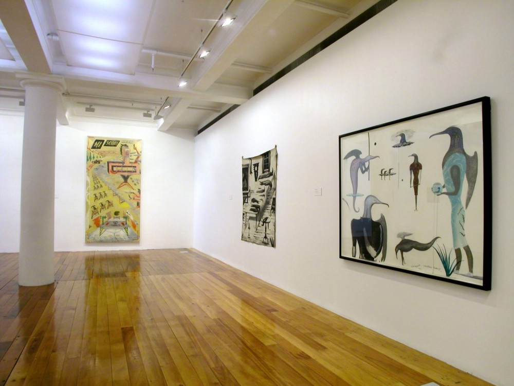 The image shows one half of a white gallery space with a polished wooden floor. A tall white column stretches from floor to ceiling on the far left of the image. To the right of this hangs a very tall vertical artwork, which depicts a composition with exaggerated perspective filled with imagery associated with radios, including antennas, a table of audio equipment, a car racing along a street and the words 'Hi Score Icon' in digitised lettering along the top of the artwork. All of this is on a mustard yellow background. On the right hand wall hang two paintings. On the left hangs a large square artwork which depicts a scene inside a home. An oblong table holds stylised birds of varying sizes and lengths stacked neatly in rows, while three more hang in a clump from the ceiling. Two taxidermied huia birds, with long beaks, are perched stiffly in a large glass vitrine to the left of the table. A glowing lamp and window looking out into a dark night are also present in the work. Across the bottom, the title of the painting, 'Buller's Tablecloth' is written in capital letters. To the right of this painting is a work filled with multiple, humanoid birds with long beaks and human arms and hands. Some have wings extending out of their backs, like angels. All are looking in different directions.