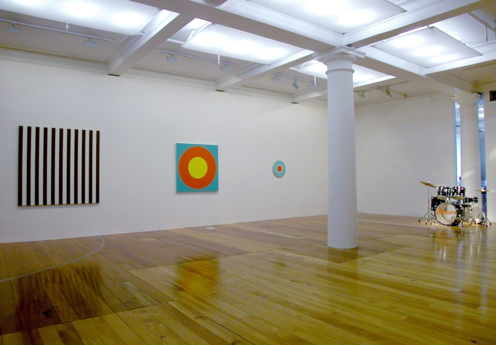 The work depicts the corner of a white gallery room with a polished wooden floor. On the left hand wall hang three artworks. The left work is a large square painting divided into even vertical strips of black and white. Next to it is a square artwork which consists of a small yellow circle within a larger orange circle, on a light blue background. To the right of this artwork hangs a much smaller circular artwork, which shows a small orange circle inside a bigger white circle inside a bigger light blue circle. Against the right hand gallery wall a full drum kit has been set up, with the words 'The Anguses' written in capital orange letters across the front of the largest drum.