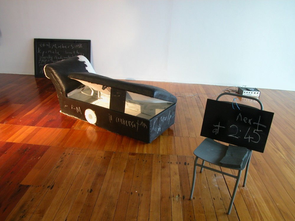 The image shows a white gallery space with a polished wooden floor. A chalkboard with indistinguishable writing scrawled all over it is propped up against the back gallery wall. In the centre of the room a couch made out of black and white animal hide is located on the floor, with the seat opened and propped up by a small chalkboard to show the inside cavity of the couch. A white speaker is placed upon it. In the centre foreground, an old fashioned student's school chair, painted black, is positioned with another chalkboard propped up on it with 'next at 2:45' scrawled on it. An eraser sits on the seat of the chair.