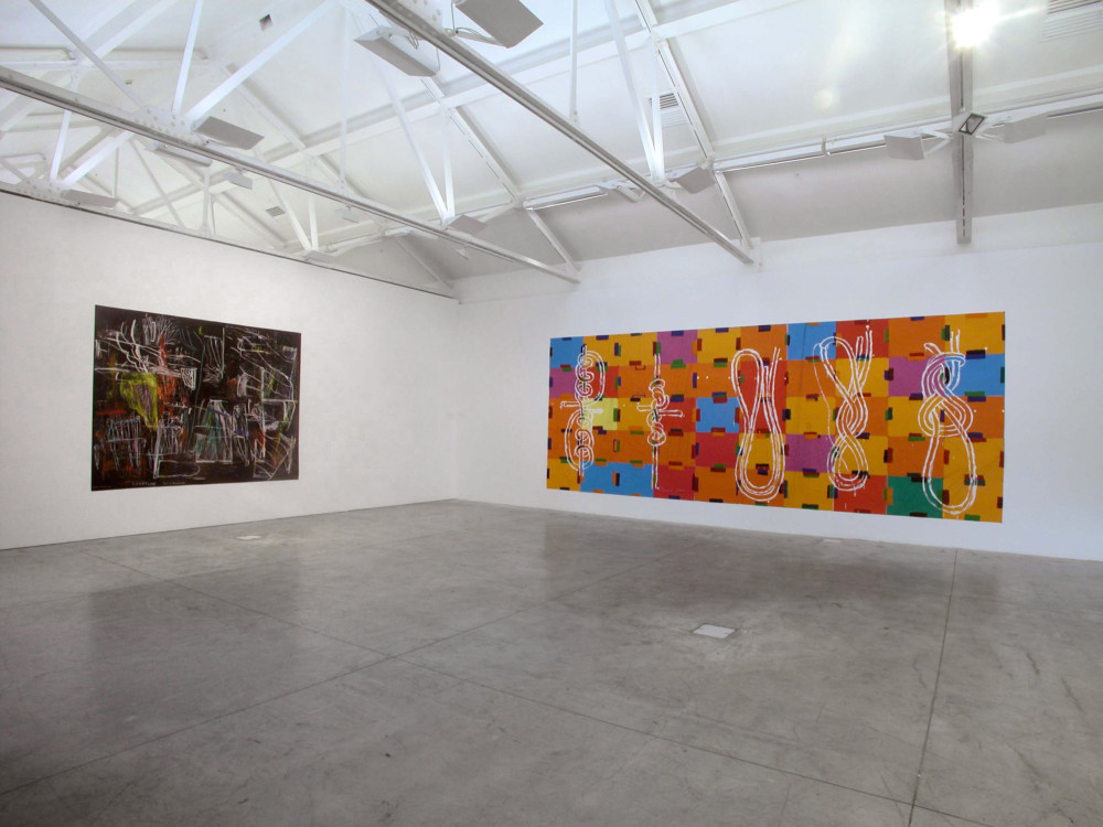 The image shows a corner of a white gallery space with a concrete floor. On the left hand wall hangs a large horizontal painting covered in messy, angular abstract white and grey lines, with multicoloured scribblings, against a red and black cloudy background. On the right hand wall hangs a very long oblong, large work consisting of tiles of blue, orange, red, purple and green with different kinds of knot diagrams painted over the top in white.