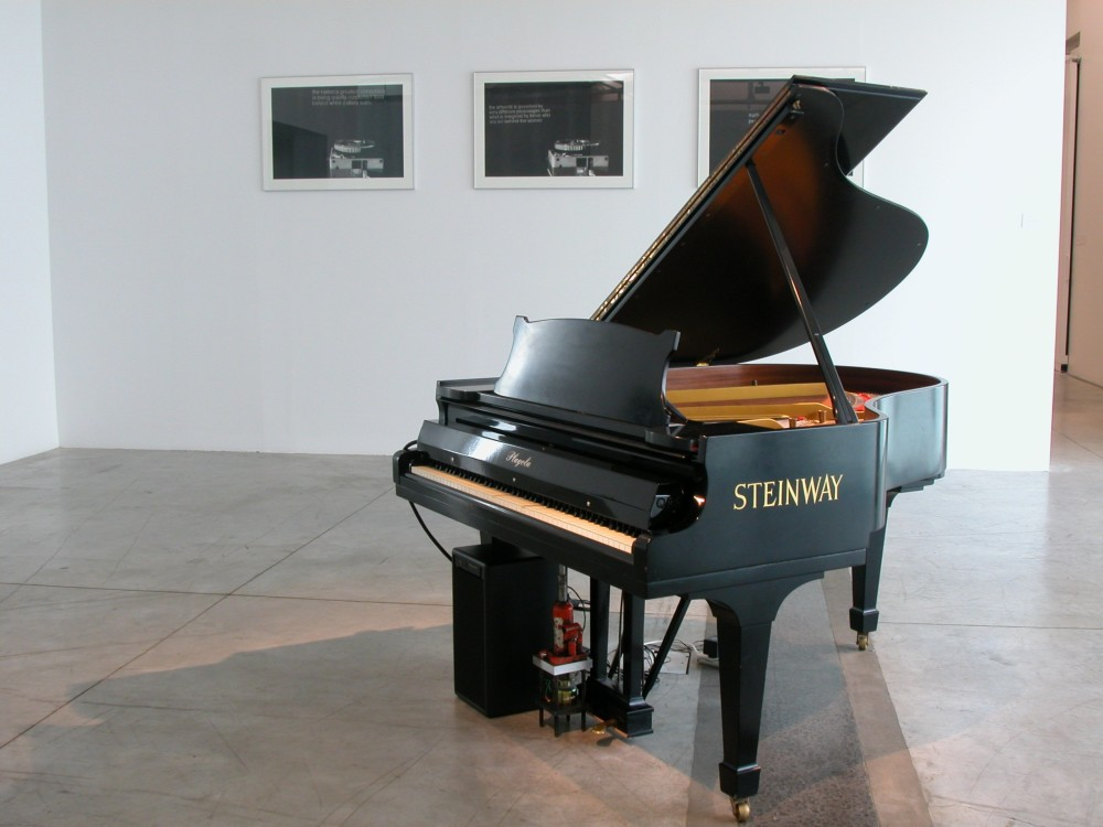 The image shows a white gallery space with a concrete floor. On the back wall hang three framed artworks, each with a circular slide holder in the foreground and small, indiscernible white text printed next to them. In the centre of the room is a large Steinway grand piano.