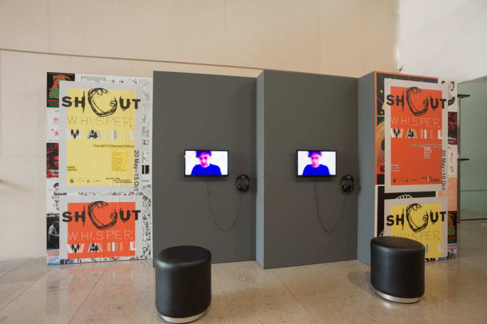 The image shows a large atrium space. Multiple freestanding temporary walls in grey are positioned in a staggered fashion. The two outside walls have promotional posters for the show on them in yellow and bright orange, while the two inner walls have small television screens mounted on them with headphones. A person in a blue shirt can be seen on the screens, taking up the whole frame so that their head and shoulders are the only parts of them visible.