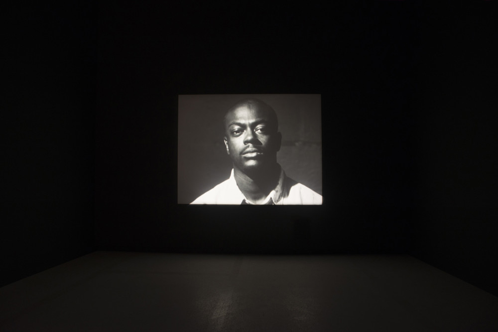 The image shows a large, dark room. In the centre of the room projected onto the back wall is a black and white image of a man with facial hair staring intently at the viewer, wearing a white shirt with collar. Only the head and shoulders of the man are visible, and he stands close to the camera taking up the frame.