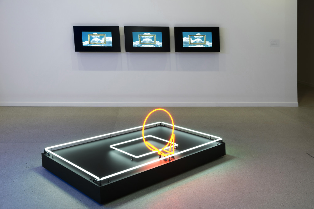 The image shows a gallery space. In the centre of the image on the floor is a large rectangular neon sculpture, comprised of a rectangular black platform outlined in white neon tubing, with a smaller rectangle in white neon in the middle. A circle of bright orange neon stands up at a 45 degree angle from this platform. On the wall behind this sculpture are three televisions, each with an image of a gold picture framed against a background of fluffy white clouds and blue sky.