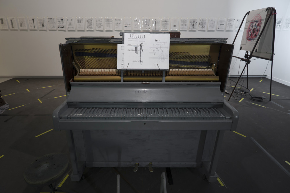 The image shows the same installation depicted in the previous image, but taken from the other side. In the centre of the image stands a large upright piano painted entirely in grey paint, with sheet music propped up on a stand above the keys. The sheet music is fragmented and has scrawls and scribbles all over it. Around the piano on the floor are the yellow off-cuts of tape circling the room, while on the wall behind the piano are multiple small drawings and prints in plastic protectors all in a row. To the right of the piano is one of the easels holding a large print.