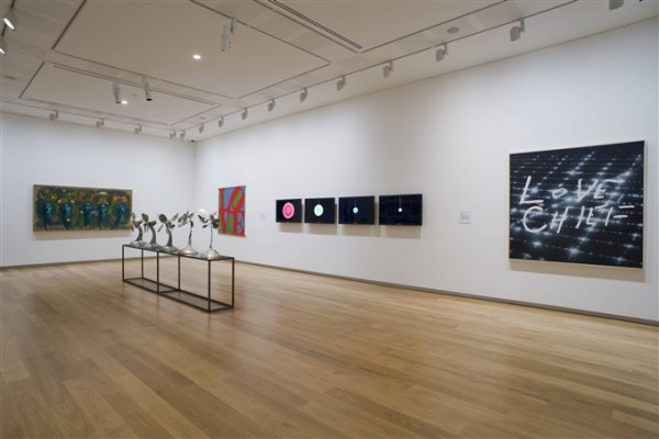 Artworks hanging on the wall in one of the second floor gallery spaces at Auckland Art Gallery. In the centre of the right hand wall, four television screens play Daniel von Sturmer's work Painted Video, in which wet paint in different bright colours is poured onto a black surface. Three works of different sizes are hung next to von Sturmer's work, and in the centre of the room is an installation of several silver plant forms on a metal rectangular structure.