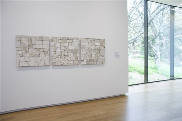 Three artworks called Web, Piece Work, and Foreign Affairs, all by Rosalie Gascoigne are shown hanging on a wall on the second floor of Auckland Art Gallery. The artworks are three square panels of the same size, all made up of irregular pieces of wood of slightly differing colours, in light ashy shades of off-white and brown. To the right of the artworks is a floor length window which looks onto Albert Park.